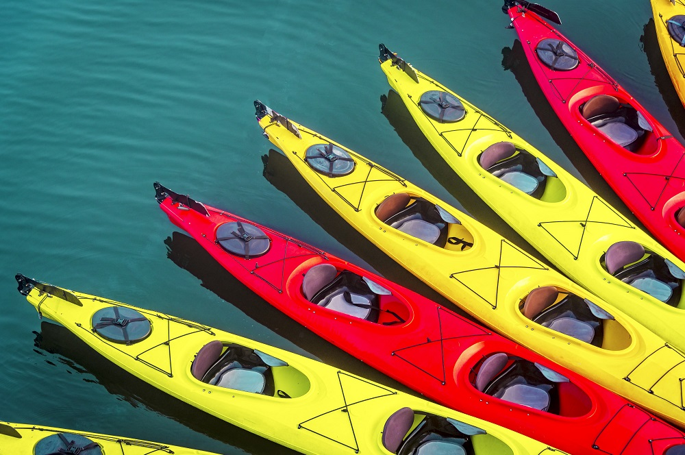 kayak background with many kayaks on the surface of the ocean with red and yellow kayaks