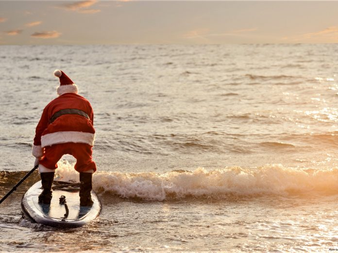 santa clause on beach surfing