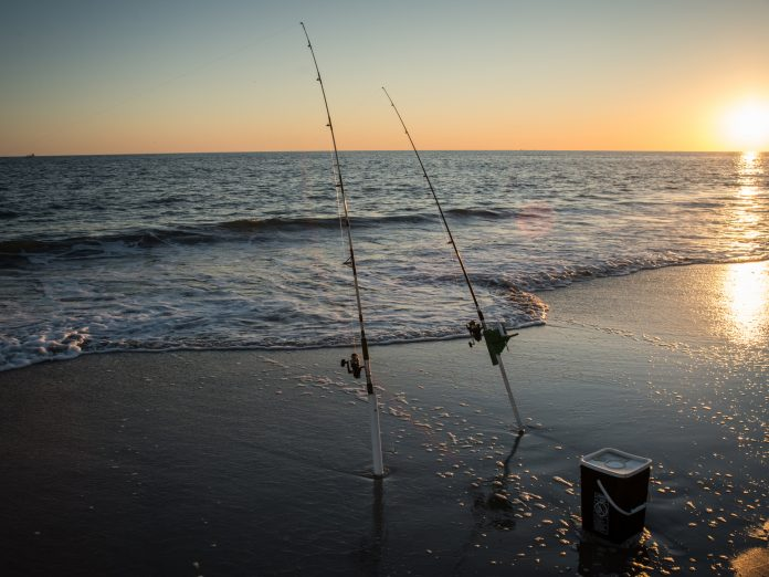 A couple of surf fishing rods stand ready at the beach in NC.