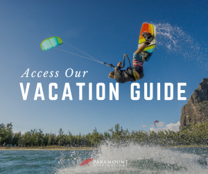 access our vacation guide text. photo of guy kiteboarding colorful board and kite on the ocean