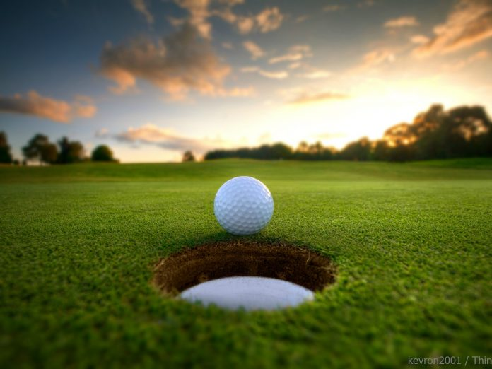 golf ball rolling into hole with beautiful sunset in the background
