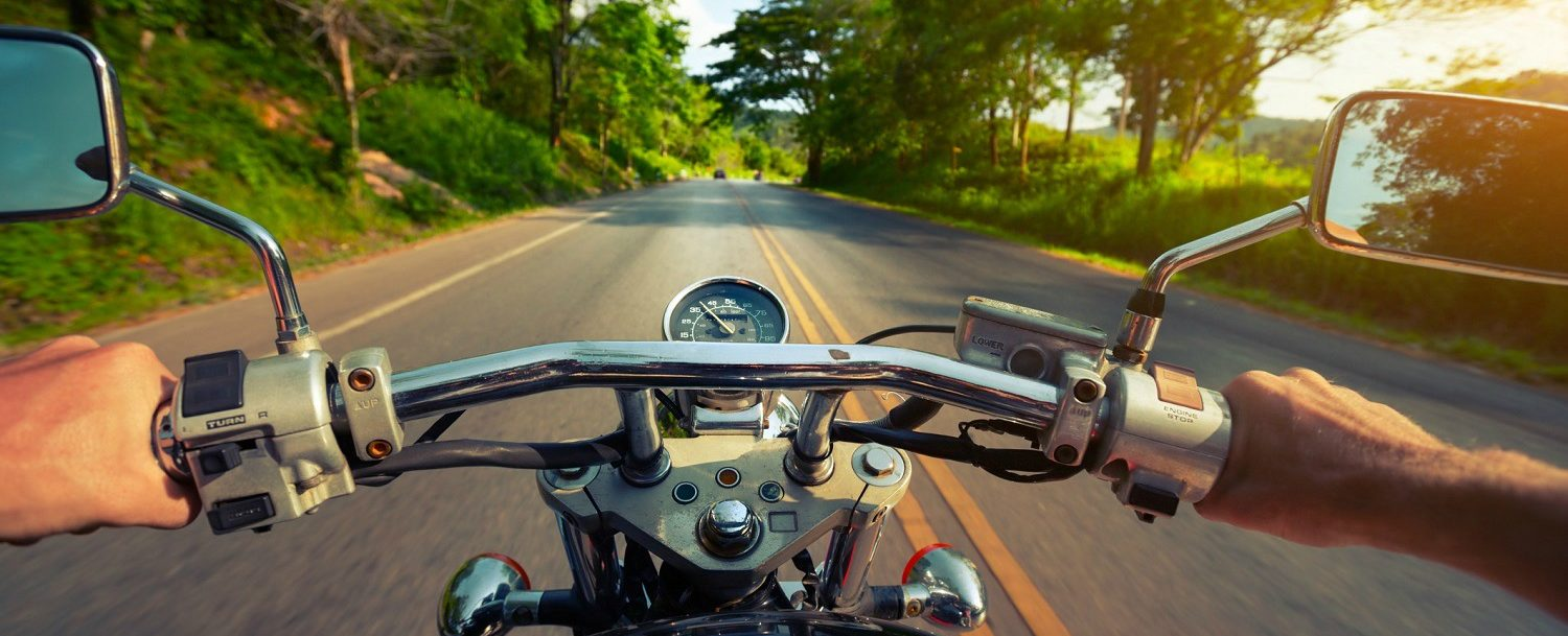 Driver riding motorcycle on an asphalt road through