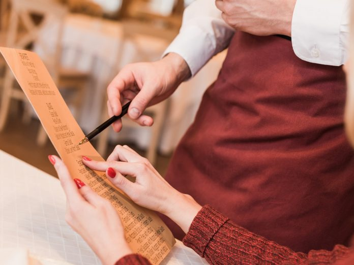 Cropped image of customer asking waiter about food in menu