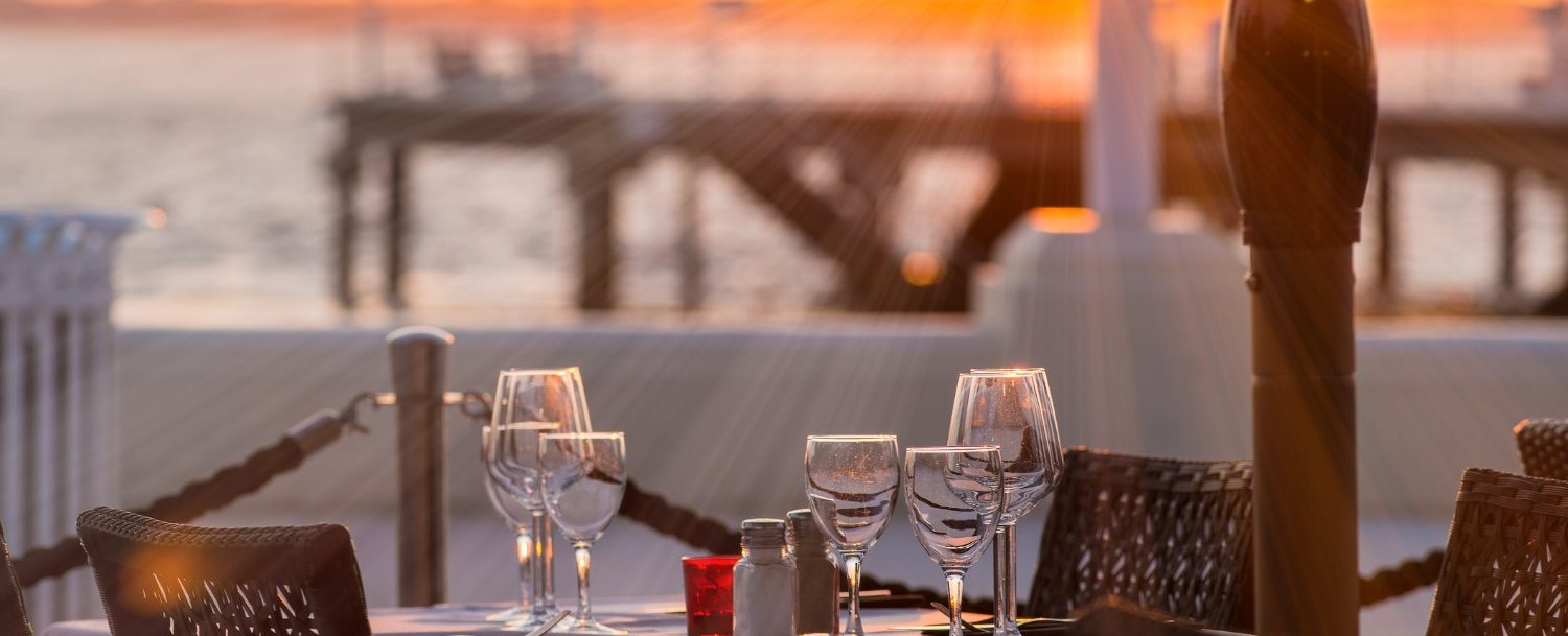 beautiful dining set up in front of a waterfront sunset setting