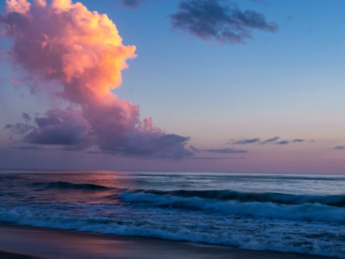 Amazing tall clouds over the ocean reflect the colors of the morning sun as it breaks over the horizon. Shades of purple, pink and blue in the sky and reflected on the water.