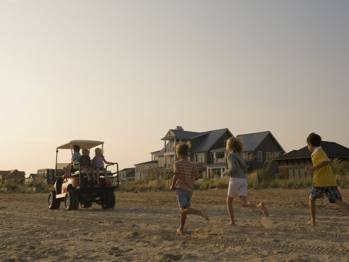 Kids running on the beach after a golf cart in the sand