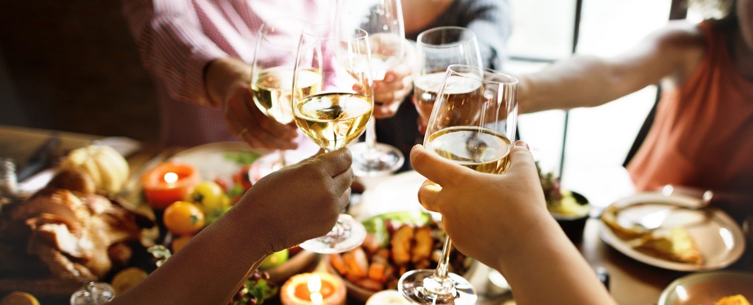 People raising glasses of wine at Thanksgiving dinner
