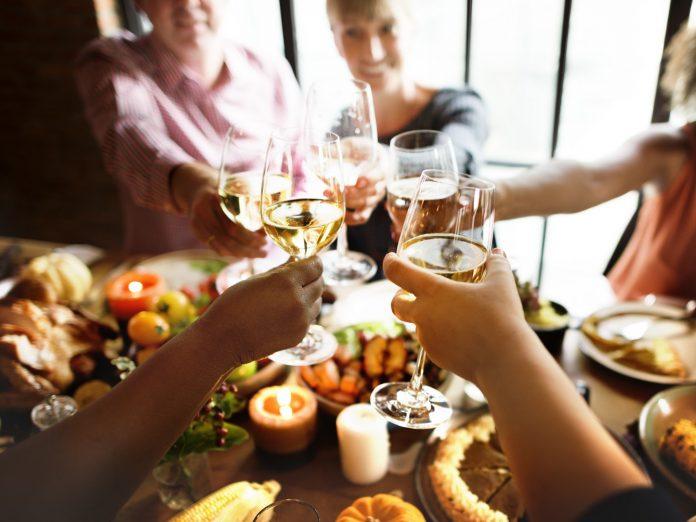 People raising glasses of wine at Thanksgiving dinner