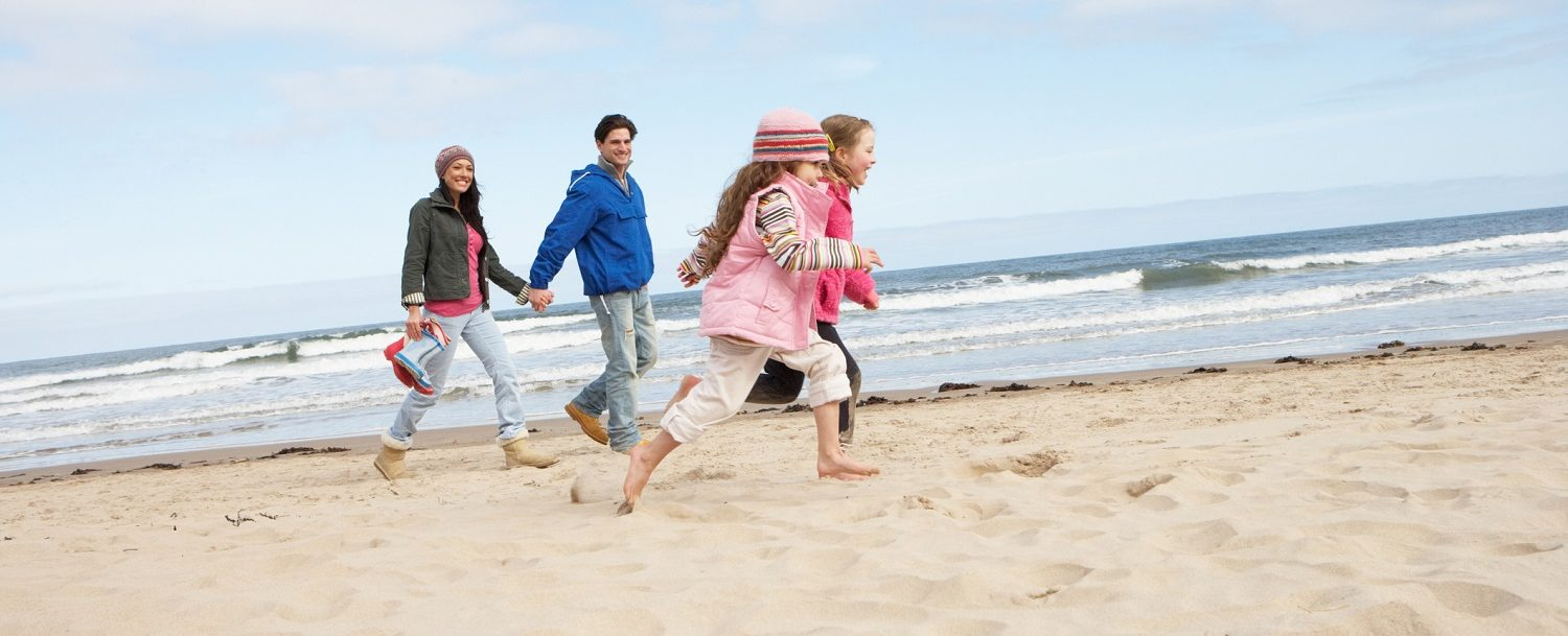 family running on beach in winter