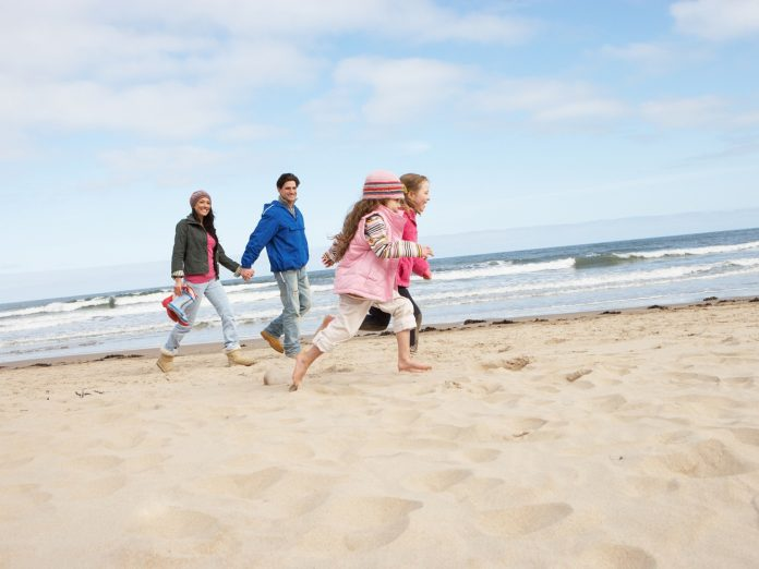 family running on beach in winter