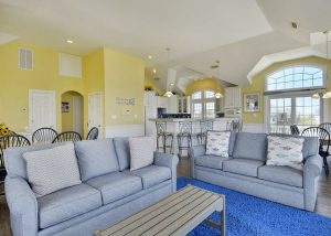 vacation rental living room, yellow walls, couches, blue rug, kitchen