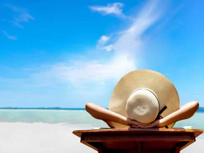 woman in floppy hat relaxing on beach