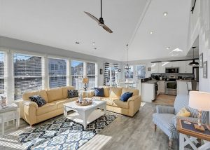 outer banks vacation rental living room with yellow couches, rug, coffee table, kitchen