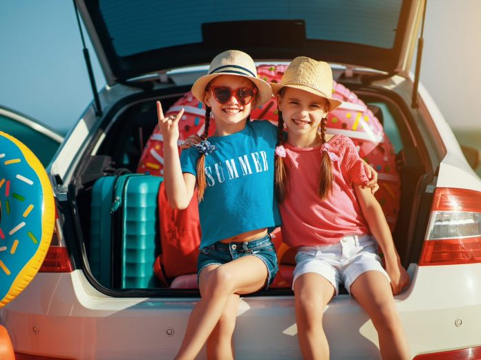 two kids smiling at the back of car, road trip, why obx is the perfect raleigh getaway